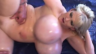 Oiled up blonde lady with huge hooters gets drilled by a muscled stud