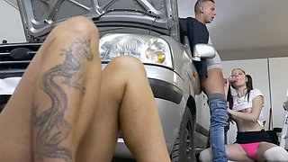 Two girls have fun with a dude in the garage next to a car