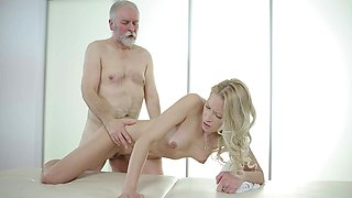 A blonde with curly hair is getting massaged by an old dude