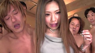 A single Japanese lady is trying to satisfy a dozen of men